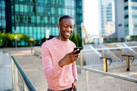 Portrait of smiling young african american man listening to music with headphones and mobile phone while walking in city