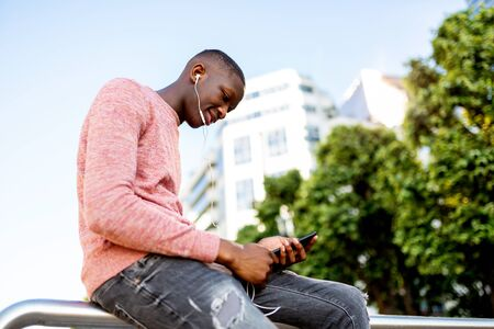 Portrait of young black man listening to music with headphones and mobile phone