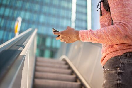 Close up african american male hands holding cellphone  in city 写真素材