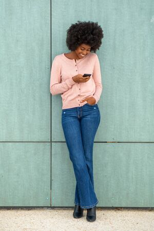 Full body portrait of happy smiling african american woman leaning against green wall and looking at mobile phone Stockfoto