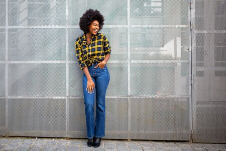 Full body portrait of trendy young african american woman with afro smiling and looking away