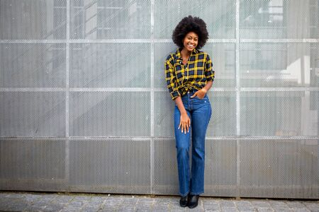 Full body portrait of stylish young african american woman with afro smiling Stockfoto