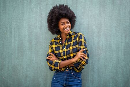 Portrait of smiling young african american woman with afro hair standing arms crossed
