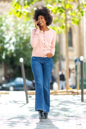 Full body portrait of happy smiling african american woman walking and talking with cellphone outside in city Stockfoto