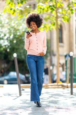 Full body portrait of happy smiling african american woman walking with cellphone outside in city
