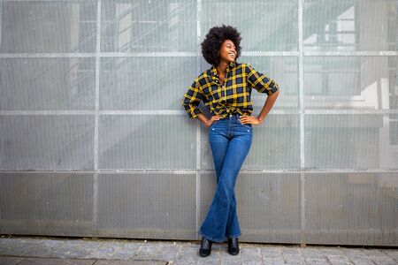 Full body portrait of fashionable young african american woman with afro smiling