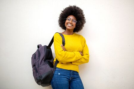 Portrait of young african american woman with afro bag glasses standing by white wall Stock fotó