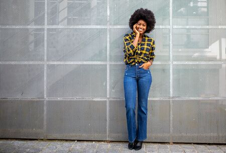Full length portrait of stylish young african american woman with afro smiling