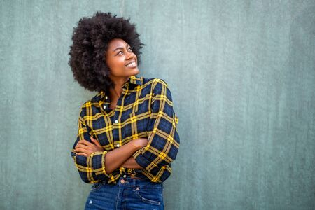 Portrait of smiling young african american woman with afro hair standing arms crossed and looking up Stock fotó