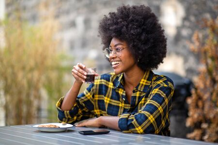 Portrait of happy young african american woman smiling with cup of coffee