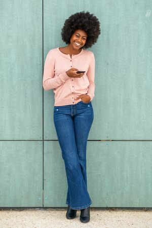 Full body portrait of happy smiling young woman leaning against green wall and looking at mobile phone Stockfoto
