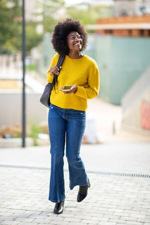 Full body portrait of happy young black woman walking with bag and mobile phone in city Stockfoto
