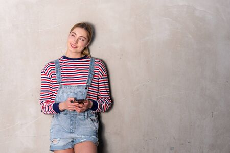 Horizontal portrait blond girl smiling with mobile phone by gray wall
