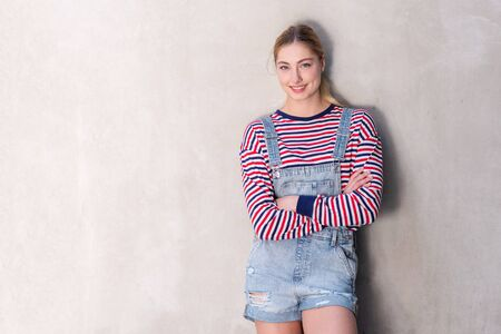 Portrait of smiling teenage girl with blond hair crossing arms by wall Stock fotó