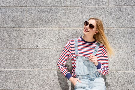 Portrait cool blond teenage girl with sunglasses smiling by wall
