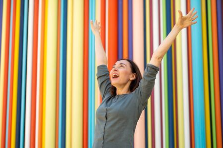 Portrait cheerful middle aged woman with arms raised by colorful background Imagens