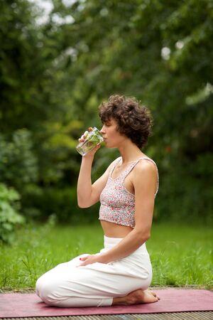 Seitenporträt der Yogafrau, die im Trinkwasser des Parks sitzt