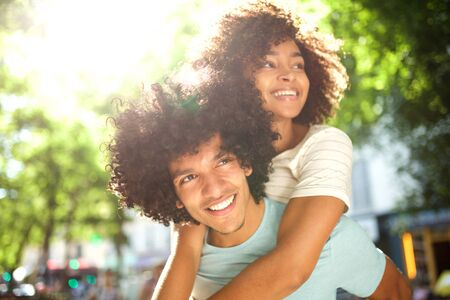 Close up portrait of smiling afro man giving piggyback to happy girlfriend outside