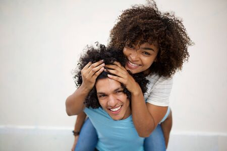 Portrait smiling african american girl piggyback and holding hair of happy afro man by white background
