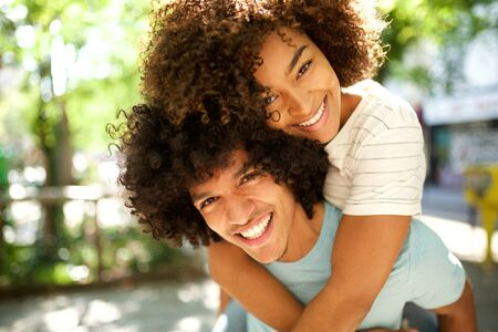 portrait of happy guy giving smiling girl piggyback outdoors