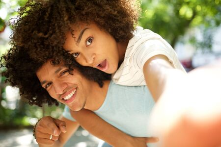 Portrait of happy young woman taking selfie while she is piggyback with smiling  guy