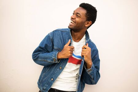 Portrait fashionable young african american man laughing with denim jacket by white wall Stockfoto