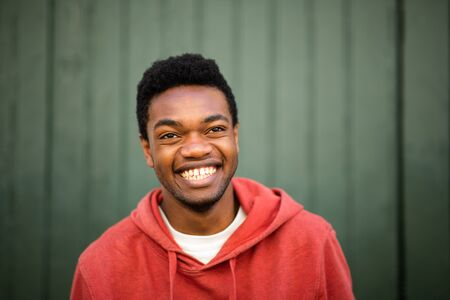 Close up horizontal front portrait of smiling african american man against green background Stockfoto