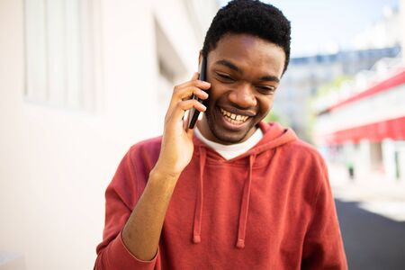 Candid portrait smiling african american man talking with cellphone outside Stockfoto
