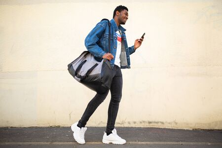 Full body portrait of happy smiling young african american man walking with bag and mobile phone on street