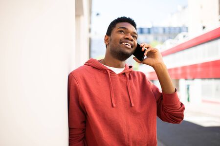 Portrait happy african american man leaning against wall talking with mobile phone outside Stockfoto
