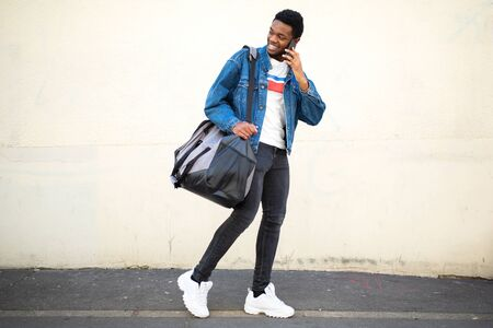 Full body portrait of happy young african american man walking with bag and talking with cellphone on street