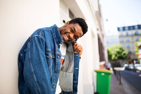 Side portrait of cool young african american man laughing with denim jacket outdoors