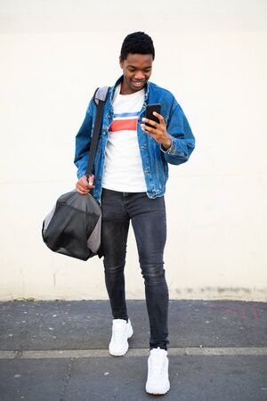 Full length portrait of happy young african american man walking with bag and cell phone on street Stockfoto
