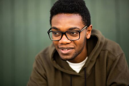 Close up portrait of handsome young african american man with glasses looking away Stockfoto