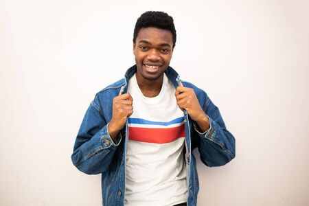 Portrait of fashionable young african american man with denim jacket by white wall