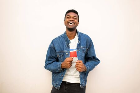 Portrait of happy african american young man laughing and looking up by white background Stockfoto