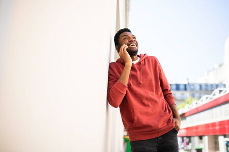Portrait happy african american man leaning against wall talking with cellphone outside