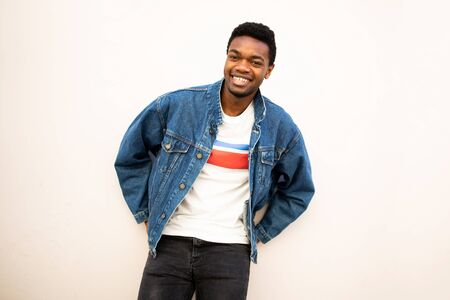 Portrait of cool african american man smiling with denim jacket leaning against white wall Stockfoto