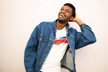Portrait of happy african american man laughing with hand behind head by white background