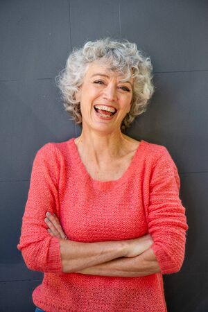 Front portrait of attractive middle aged woman laughing with arms crossed