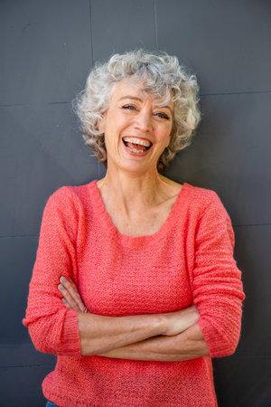 Vorderes Porträt einer attraktiven Frau mittleren Alters, die mit verschränkten Armen lacht Standard-Bild