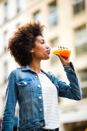 Portrait happy young black woman drinking from juice bottle in city Stock Photo