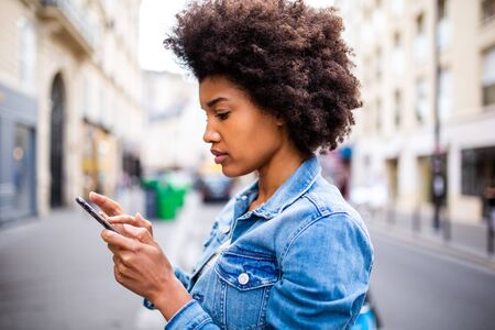 Side portrait of young black woman with afro hair sending text message on cellphone