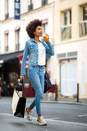 Full body portrait of happy young woman walking in city with shopping bag and drink