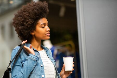 Close up portrait of young black woman with bag and cup of coffee