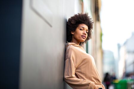 Portrait beautiful black female fashion model with afro hairstyle leaning against wall Stock fotó