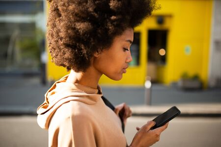 Close up side portrait of beautiful young black woman with afro hairstyle walking with cellphone in city Stock fotó