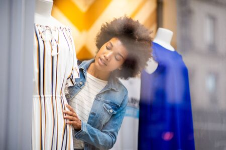 Portrait of beautiful young black woman shopping for clothes in store