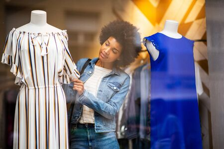 Portrait of young black woman shopping for clothes in store