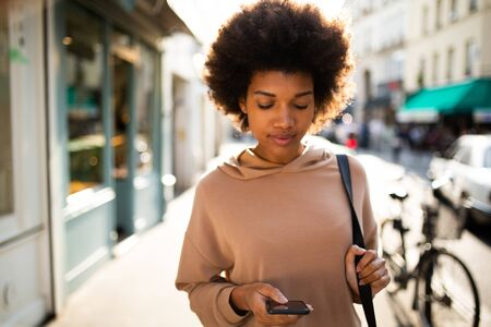 Portrait of young black woman walking with mobile phone in city